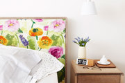 Small nightstand and swing-lamp next to the floral headboard.