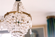 A crystal chandelier suspended from a white ceiling