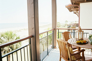 A balcony with outdoor furniture overlooking the ocean