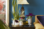 A side table holding a decorative lamp and floral arrangements.