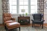 A traditional living room with a brown leather lounge chair.