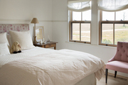 Window light white bedding with flower headboard.