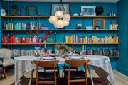 This dining room makes a bold statement with turquoise walls, a mid-century chandelier, and colorful books.