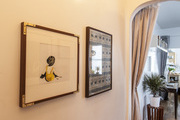 Framed art and hanging light fixtures line a long hallway in a Brooklyn apartment