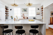 A white kitchen with black stools.