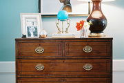 A brown lamp, a vase of flowers, and decorative objects atop a wooden chest