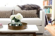 A contemporary coffee table with a gold tray.