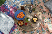 A wooden picnic table on Kantha throws in a Los Angeles backyard