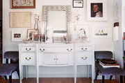 A gallery wall of art hung above a white sideboard and a pair of chairs