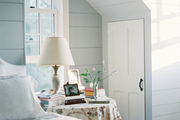 A skirted bedside table topped with books in a light-gray bedroom