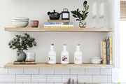 Wooden storage shelves to show off the kitchen's cooking essentials, such as ceramic bowls, cook books, vases, and glasses.