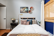 Globally inspired bedroom with blue accent wall and soft textiles.