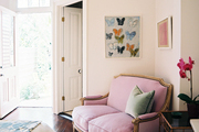 A pink settee and a brass chandelier surrounded by art in a bedroom