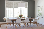Large white windows behind contemporary dining room furniture.