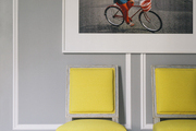 Two Louis-style chairs upholstered in yellow fabric under a Slim Aarons photograph