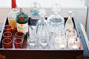 A tray of bar essentials atop a storage trunk
