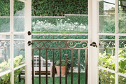 French doors leading to a balcony covered by a black-and-white-striped awning