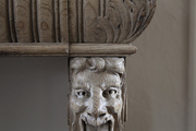 A carved-wood gargoyle atop a leg of a sculptural sideboard in a Hamptons home