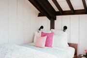 Rustic wood beams balanced by cheerful blue-and-white bedding in a guest room