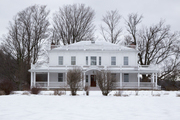 A traditional white home in winter.