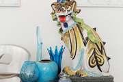 An antique foo dog amid glassware and ceramics on a red console