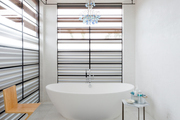 A standalone tub with a chandelier above it.