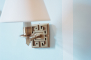 A brass sconce with a white shade on blue walls
