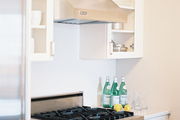 Glass-fronted white cabinetry paired with stainless-steel appliances