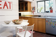 A white table and chairs in the corner of a kitchen