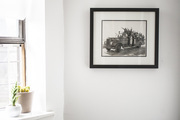 A framed black and white photograph on a white wall