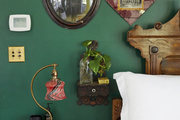 Vintage decorations hang on a deep green wall.