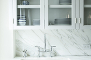 A gray-veined marble backsplash and countertop in a contemporary kitchen
