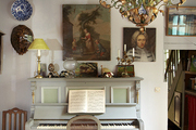 Framed art hanging above upright piano.