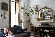 Whitewashed brick walls and bleached wood floors in a compact NYC apartment.