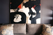 A painting hung above a gray couch with a pair of pillows