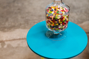A glass urn of jelly beans on a blue-and-yellow table at Jessica Alba's Honest Company office