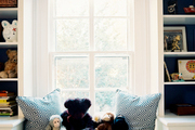A window seat with a roman shade between white built-in bookcases