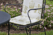 A seat cushion made of all-weather fabric on a wrought iron chair in a garden