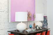 Red midcentury dining chairs at a table with white table lamps under a minimalist artwork