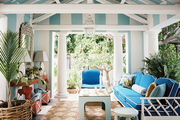 A striped pavilion filled with blue outdoor furniture