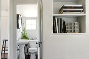 Built in shelving and archway leading to bathroom.