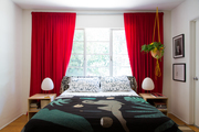 An eclectic bedroom with red curtains and white walls.