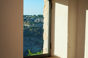 A gray linen shade hung above a window with views of the Italian countryside