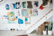 Abstract paintings hanging near a stairway.