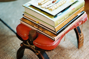 A camel saddle topped with a stack of books and a tray of pens