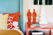A blue headboard and a red bedside table topped with a pagoda-style lamp