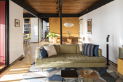 A mid-century modern living space with custom rug and muted green sofa.