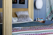 An eclectic bedroom with blue walls.