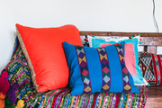 Moroccan pillows and blanket on primitive wooden bench.