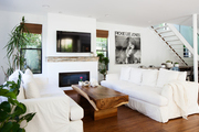 A mostly white living room with a live-edge wooden coffee table.